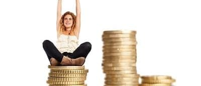young woman doing a winner gesture sitting on a coins pile