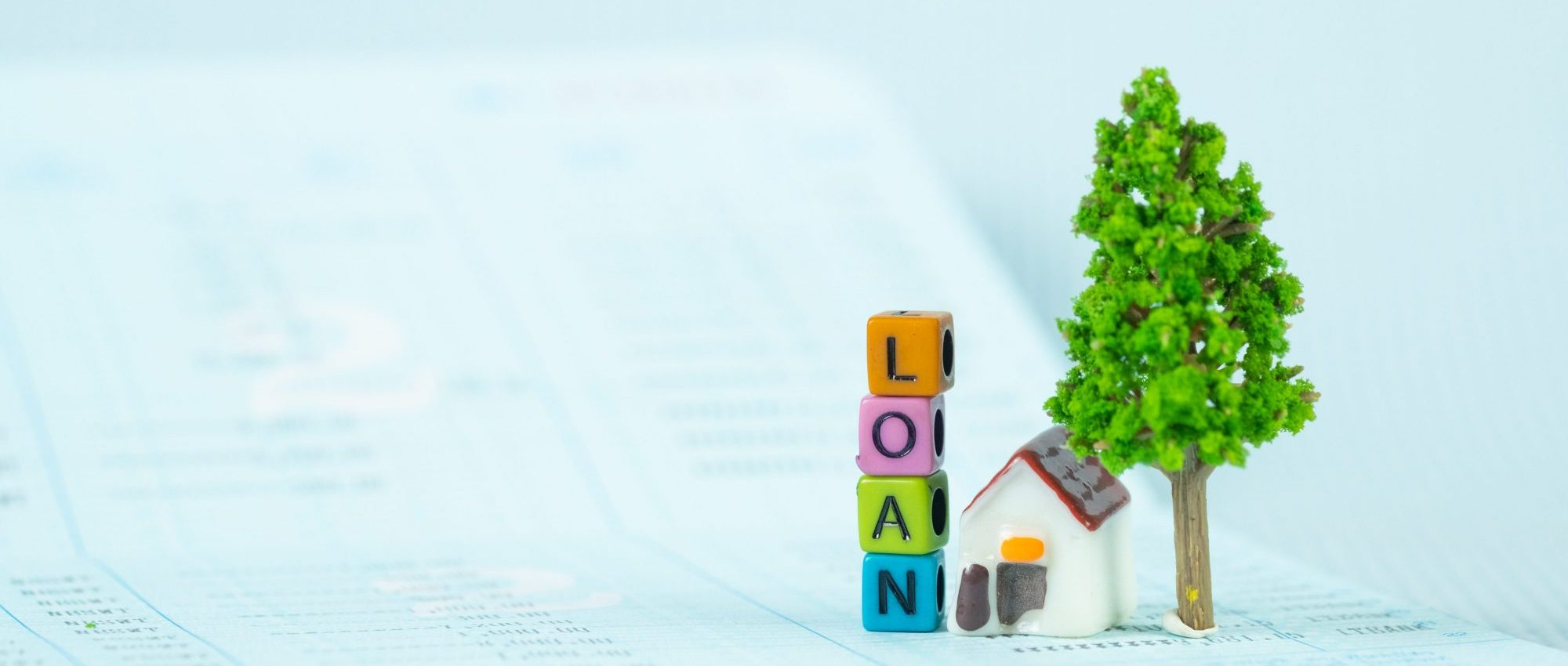 LOAN text and small model house and little tree with notebook, savings banking, loan for house and real estate concept idea.
