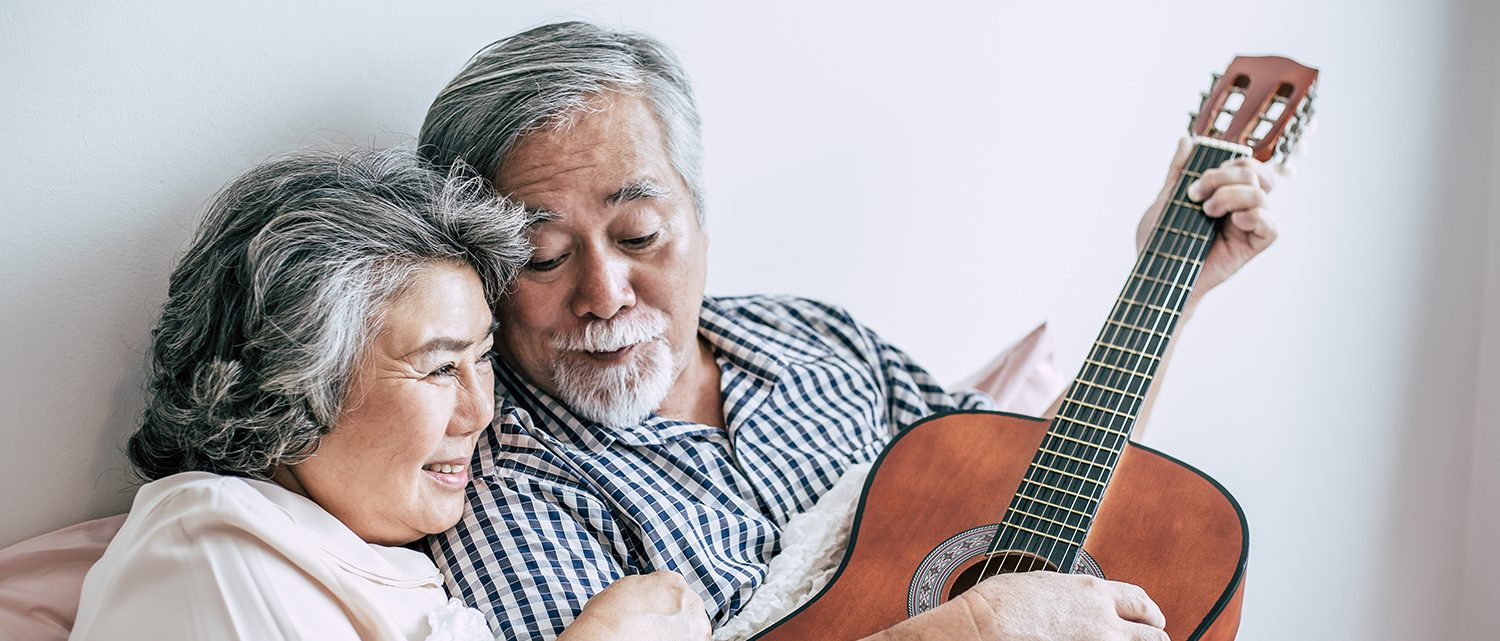 Senior couple relax playing acoustic guitar in bed room