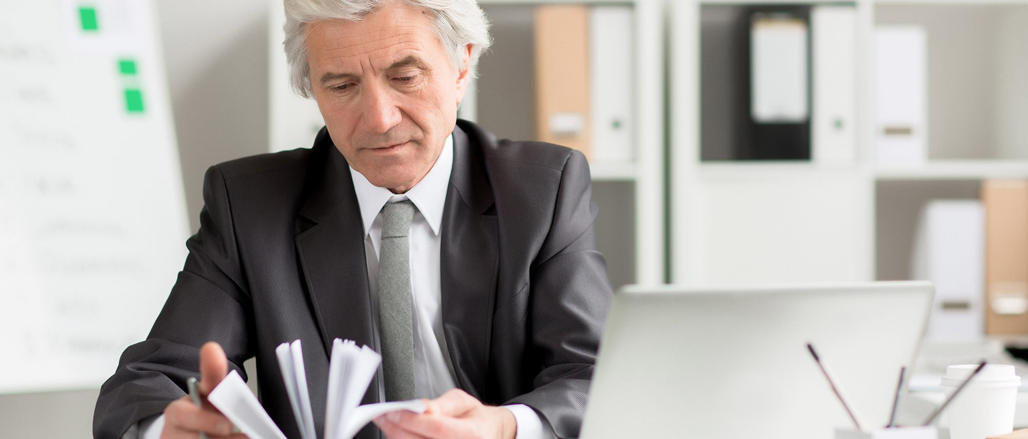 Grey-haired businessman in formalwear looking for some specific notes in his notebook by workplace