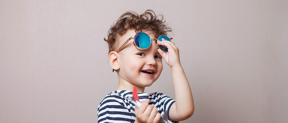 Infant, child with a toy airplane in his hands and sunglasses. Family law concept.